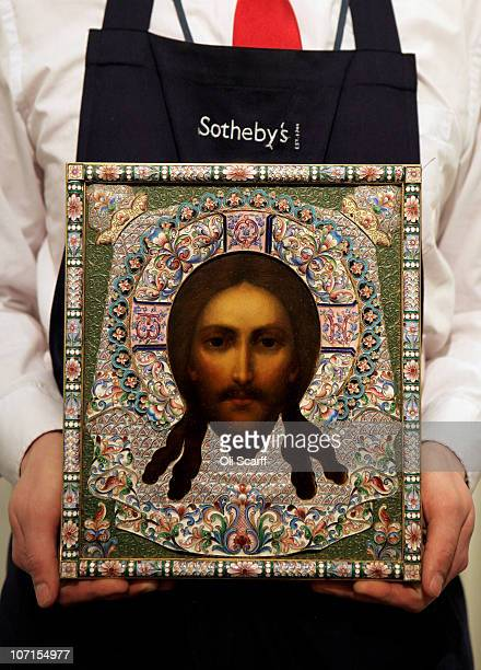 A gallery assistant for Sotheby's Auction House admires a silver and enamel icon of the Mandylion Orest Kurlyukov from Moscow made around 1899 which...