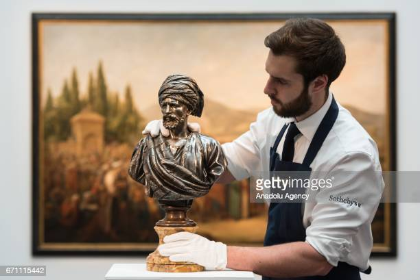 Gallery assistant holds a bronze statue titled Cheik Arabe du Caire by artist Charle-Henri-Joseph Cordier showing at the London press view of...