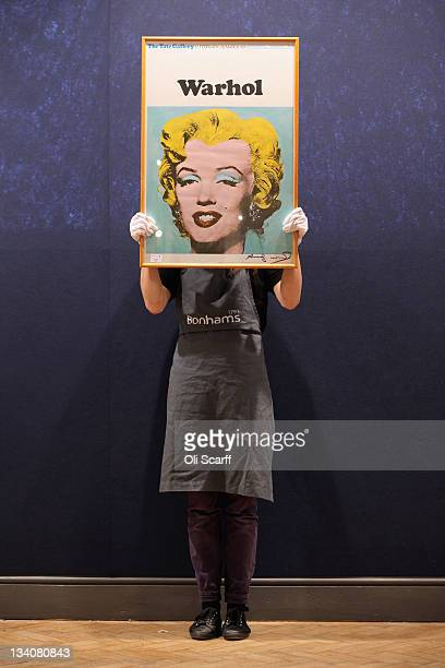 A gallery assistant holds a print of an Andy Warhol artwork estimated to fetch 1500 GBP in Bonhams auction house on November 25 2011 in London...