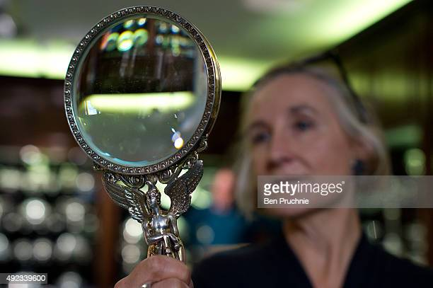 Gallery assistant holds a silver gilt magnifying glass bearing a figure of Hermes holding a golden apple during the Paul Storr Regency Silverware...