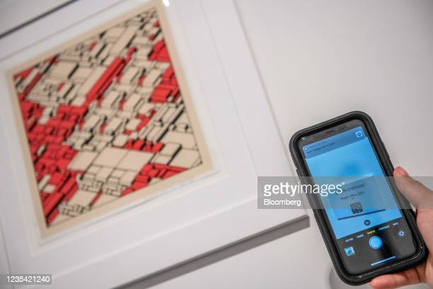 Gallery assistant holds a smartphone scanning a QR code for NFT Kjetil Gold by Archetype next to a physical print of the work arranged, during the...