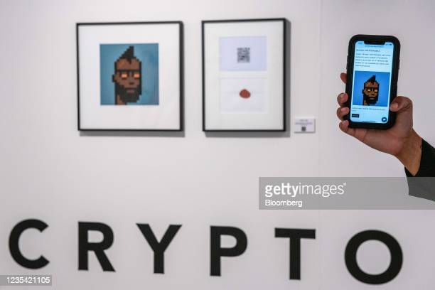 """Gallery assistant holds up a smartphone displaying the gallery's online marketplace near an NFT and signed lithograph """"Sealed Cryptopunk"""" by Larva..."""