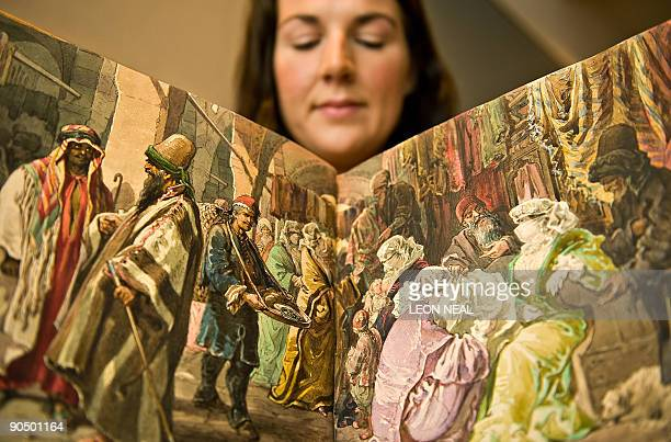 Gallery assistant holds up sketchbook of watercolours by Count Amadeo Preziosi at Bonham's auction house in central London, on September 9 depicting...