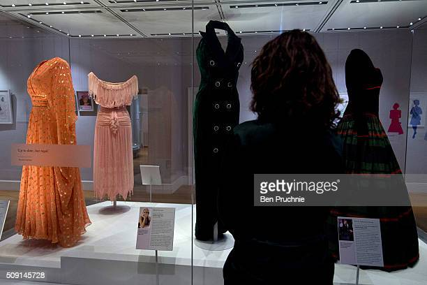 A gallery assistant looks at a collection of dresses worn by Princess Diana at the Fashion Rules Exhibition at Kensington Palace on February 9 2016...