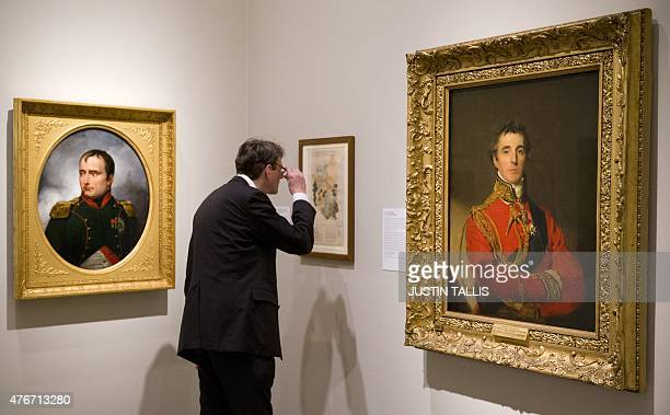 Gallery assistant looks at a painting between a portrait of Arthur Wellesley, Duke of Wellington , by British artist Thomas Lawrence and a portrait...