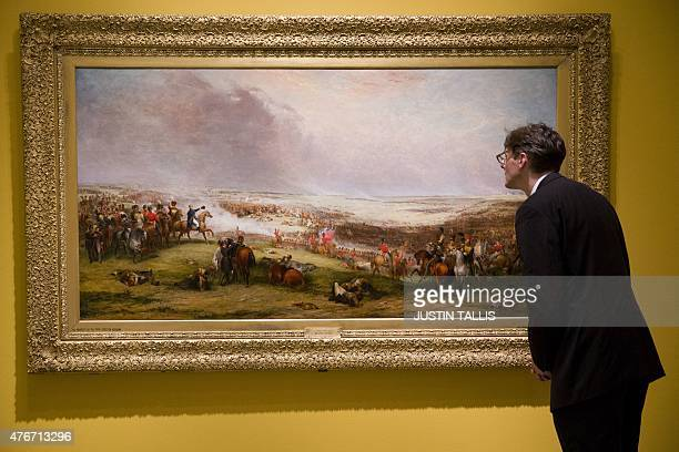 A gallery assistant looks at a painting entitled 'Battle of Waterloo 1815' by George Jones in the 'Wellington Triumphs Politics and Passions' exhibit...