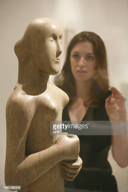 A gallery assistant looks at a work by British Sculptor Henry Moore entitled Girl 1931 as she poses for a photograph at the Royal College of Art in...