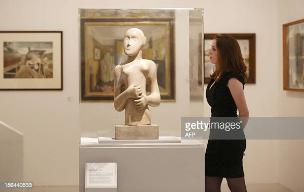 A gallery assistant looks at a work by British Sculptor Henry Moore entitled Girl 1931 as she poses for a photograph during an exhibition at the...
