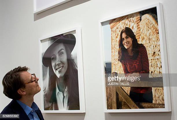 Gallery assistant looks at two new portraits of Catherine, Duchess of Cambridge, taken in the Norfolk Countryside by British photographer Josh Olins,...