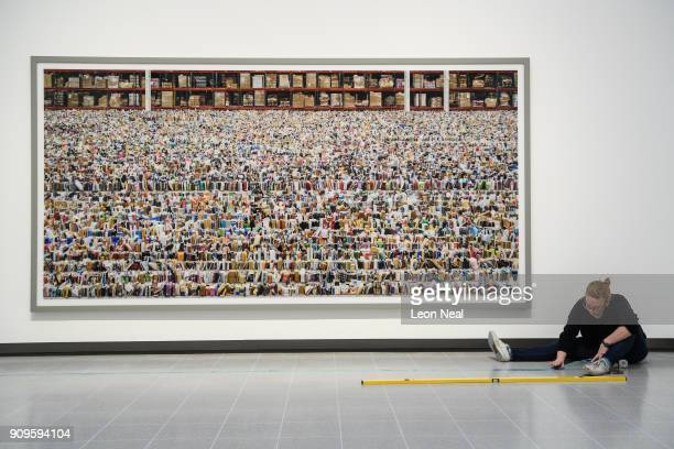 A gallery assistant makes final preparations to a floor marker as she sits in front of 'Amazon' by Andreas Gursky in the reopened Hayward Gallery on...