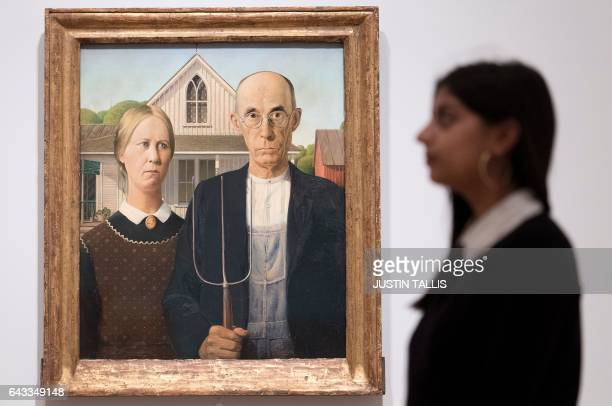 A gallery assistant poses alongside an artwork entitled 'American Gothic' by US painter Grant Wood during a photocall to promote the forthcmoing...