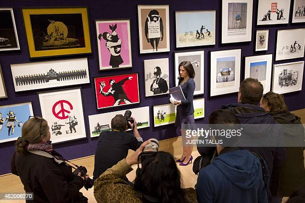 Gallery assistant poses for a picture before the media with part of a collection of 30 Banksy prints owned by the British gallery owner, Steve...