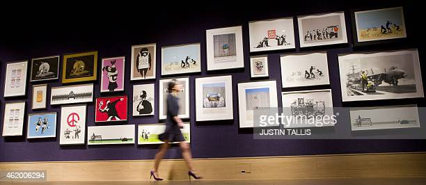 Gallery assistant poses for a picture with a collection of 30 Banksy prints owned by the British gallery owner, Steve Lazarides, at Bonhams auction...