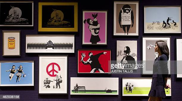 Gallery assistant poses for a picture with part of a collection of 30 Banksy prints, including the well-known 'Rage, Flower Thrower' , owned by the...
