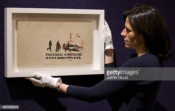 """Gallery assistant poses for a picture with """"Precision Bombing"""", one of 30 Banksy prints owned by the British gallery owner, Steve Lazarides, at..."""