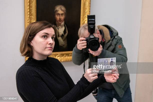 Gallery assistant poses for photographs with the new twenty pound note in front of J.M.W. Turner's self-portrait from 1799 at Tate Britain on...