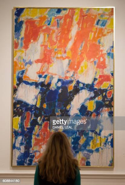 A gallery assistant poses in front of a painting entitled 'Untitled' 1956' by US artist Sam Francis during a photocall to promote Abstract...