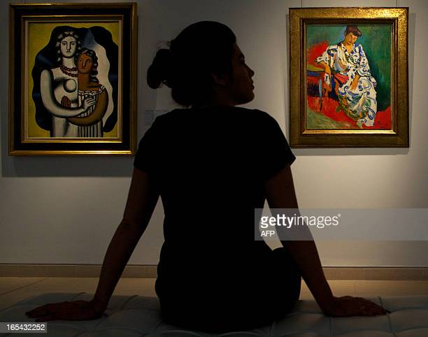 A gallery assistant poses in front of the painting 'Madame Matisse au Kimono' by French artist Andre Derain at Christie's auction house in London on...