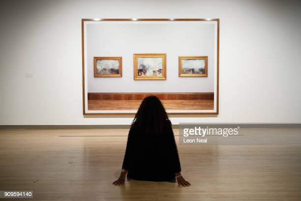 A gallery assistant poses in front of Turner Collection by Andreas Gursky in the reopened Hayward Gallery on January 24 2018 in London England...