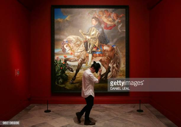 A gallery assistant poses next to an artwork entitled Equestrian Portrait of King Phillip II by US artist Kehinde Wiley on display during a photocall...