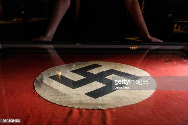 A gallery assistant poses with a captured Nazi swastika flag signed by original members of the SAS listing their missions in Africa during World War...