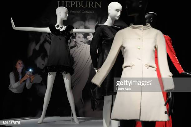 A gallery assistant poses with a Givenchy satin cocktail gown during a preview of items from the sale of actrees Audrey Hepburn's personal collection...
