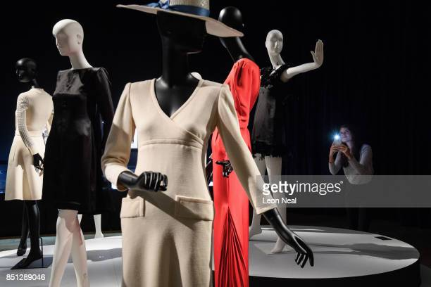 A gallery assistant poses with a selection of dresses during a preview of items from the sale of actrees Audrey Hepburn's personal collection at...