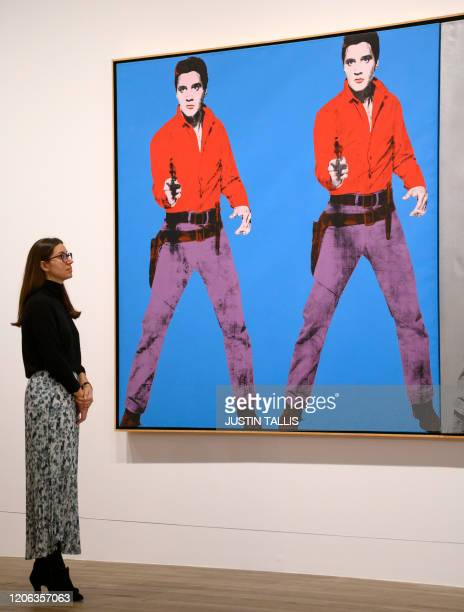 A gallery assistant poses with an artwork entitled Elvis 1 19634 by US artist Andy Warhol during a press preview for the forthcoming Andy Warhol...