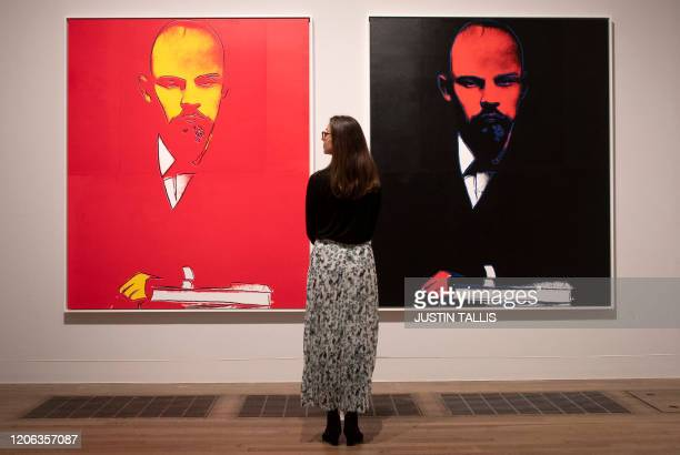 A gallery assistant poses with an artwork entitled Lenin 1986 by US artist Andy Warhol during a press preview for the forthcoming Andy Warhol...
