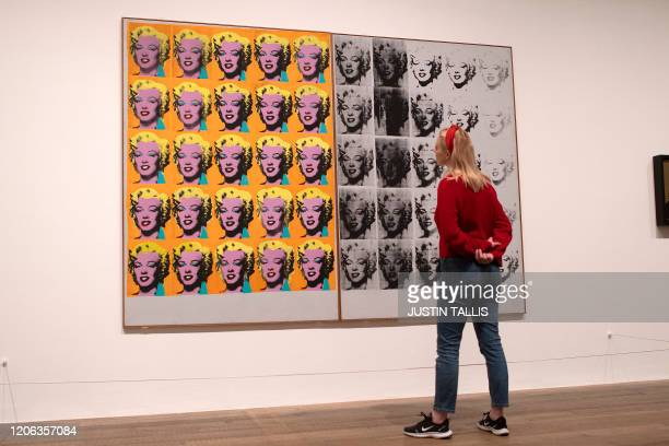 A gallery assistant poses with an artwork entitled Marilyn Diptych 1962 by US artist Andy Warhol during a press preview for the forthcoming Andy...