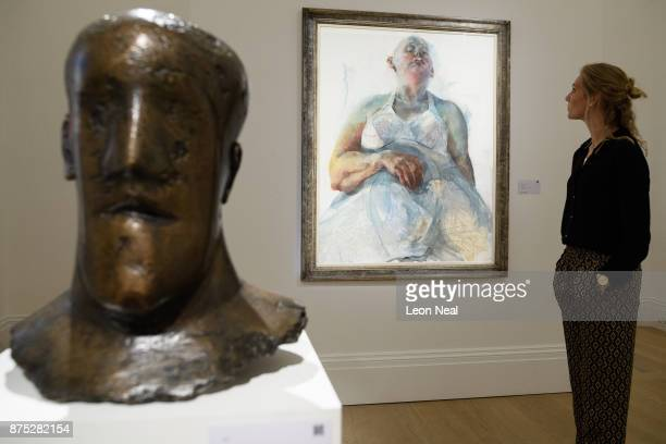 A gallery assistant poses with Head by Dame Elisabeth Frink and Cultural Fetish by Jenny Saville at Sotheby's auction house on November 17 2017 in...
