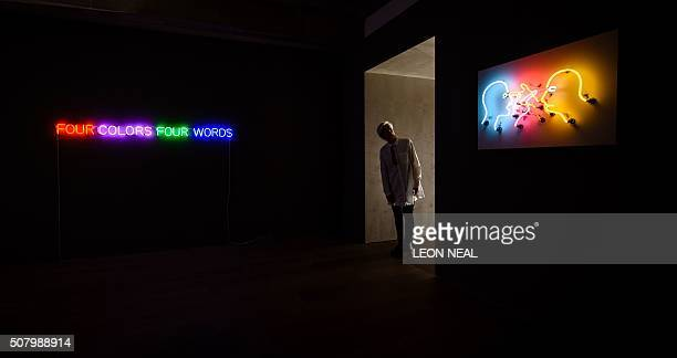 "Gallery assistant poses with neon artworks ""Four Colors Four Words"" by Joseph Kosuth and ""Double Poke In Th Eye II"" by Bruce Nauman as part of the..."