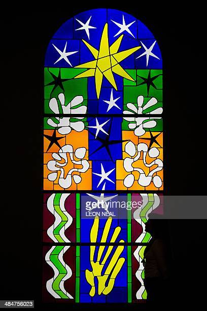 """Gallery assistant poses with """"Nuit de Noel"""", a stained glass artwork by Henri Matisse at the """"Henri Matisse: The Cut-Outs"""" exhibition at the Tate..."""