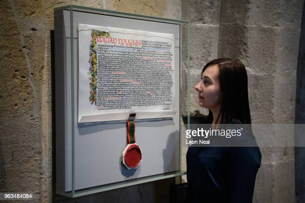 A gallery assistant poses with the marriage licence of Prince William and Kate Middleton in the Queen's Diamond Jubilee gallery at Westminster Abbey...