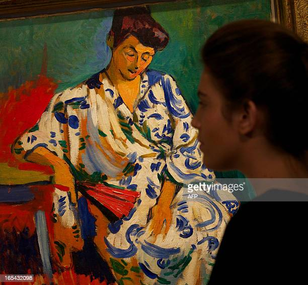 A gallery assistant poses with the painting 'Madame Matisse au Kimono' by French artist Andre Derain at Christie's auction house in London on April 4...