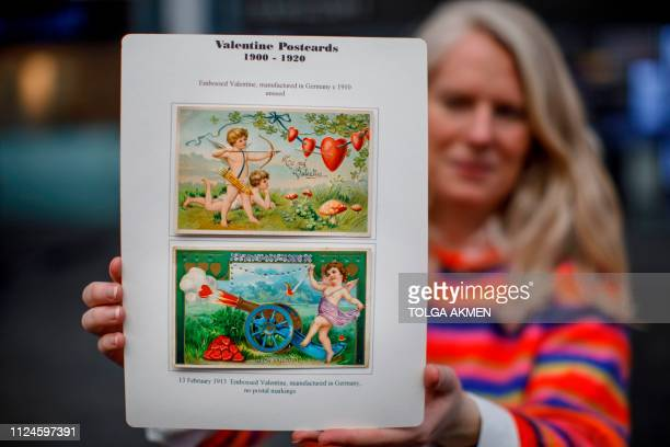 A gallery assistant poses with Valentine's Day cards from Germany dates 1910 and 1913 during the press preview of the Stampex International...