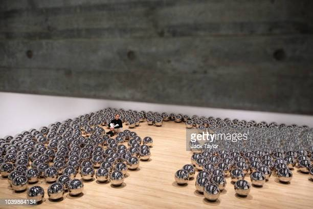 A gallery assistant sits among the stainless steel spheres which make up 'Narcissus Garden' 1966 by Yayoi Kusama during a media preview for the Space...