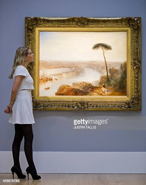 A gallery assistant studies a painting by British artist Joseph Mallord William Turner entitled 'Rome from Mount Aventine' at Sotheby's auction house...