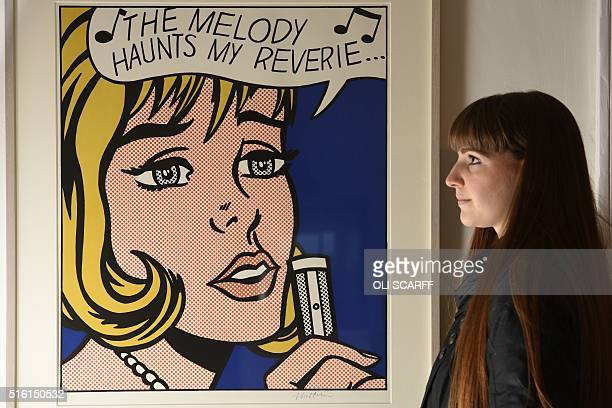 A gallery assistant studies an artwork by Roy Lichtenstein entitled 'The Melody Haunts My Reverie' an exhibit featuring in the 'At Home' exhibition...