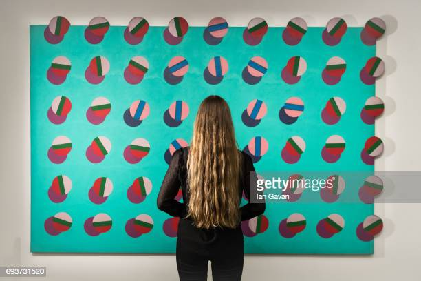 A gallery assistant views 'Giant' oil on shaped canvas 1950 by Derek Boshier as part of the Modern Post War British Art exhibition at Sotheby's...