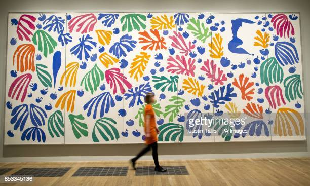 A gallery assistant walks past The Parakeet and the Mermaid 1952 by Henri Matisse at The CutOuts exhibition at the Tate Modern London