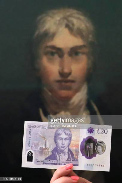 Gallery assistants display the new twenty pound note wich features British painter JW Turner in front of Turners self-portrait, which forms part of...