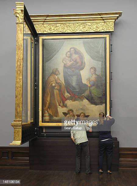 "Gallery assistants finish hanging the ""Sistine Madonna"" painting by 16th century Italian painter Raphael in its new frame at the Galerie Alte Meister..."