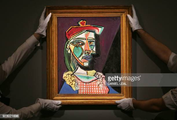 Gallery assistants hold an artwork by Spanish artist Pablo Picasso entitled 'Femme au beret et a la robe quadrillee' with an estimate price in the...
