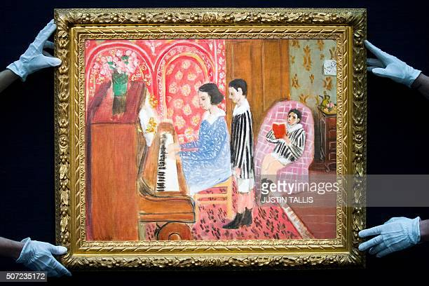 Gallery assistants pose for a photograph with a painting entitled 'La Lecon de Piano' by French artist Henri Matisse during a photocall at Sotheby's...