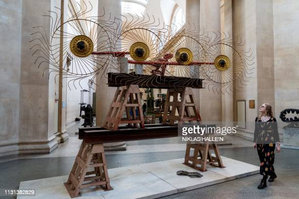 """Gallery assistants pose for a photograph with items forming an installation entitled """"The Asset Strippers"""" by British artist Mike Nelson, during a..."""