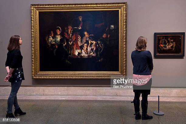 Gallery assistants pose for photographers next to the newly installed Joseph Wright Sketch at Tate Britain on March 30 2016 in London England...