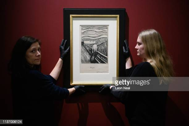 Gallery assistants pose for photographers with a lithograph print of 'The Scream' by Edvard Munch during a press event to promote the 'Edvard Munch...
