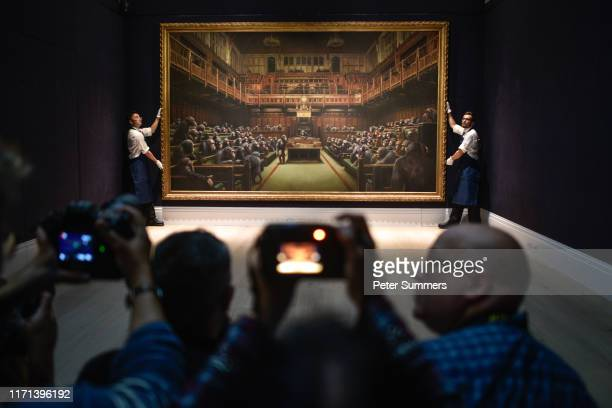 Gallery assistants pose with the Banksy painting 'Devolved Parliament' at Sotheby's on September 27 2019 in London England Banksy's dystopian view of...