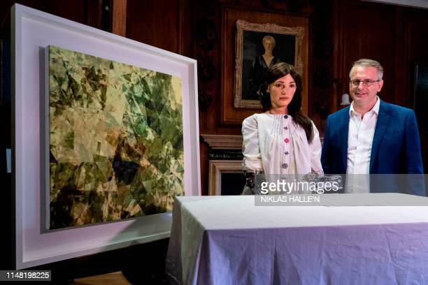 Gallery Director and inventor of AiDa the AI humanoid robot artist Aidan Meller poses with AiDa and an oil on canvas painting created by other...